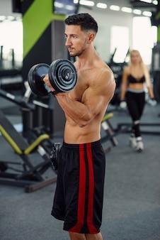 Sportieve fitness man doet oefeningen voor biceps met behulp van halters op de stijlvolle sportschool