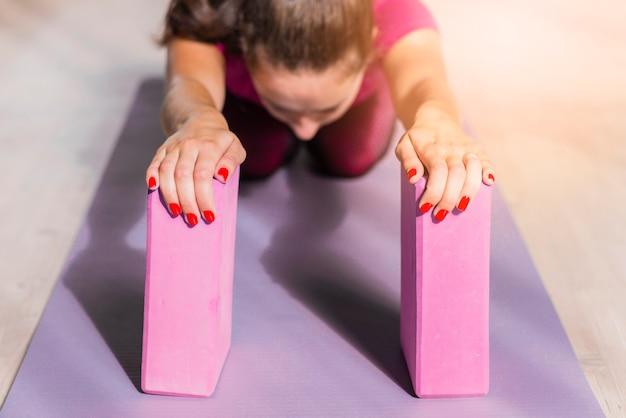Sportieve fitness vrouw beoefenen van yoga met roze blokken op oefening mat