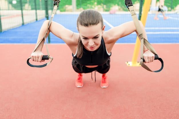 Sportieve fitness vrouw doet trx training buiten op het stadion