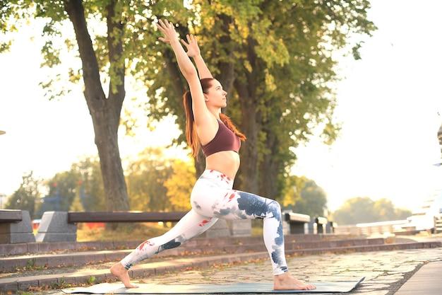 Sportieve geconcentreerde vrouw die yoga beoefent, in anjaneyasana pose staat, traint in het park bij zonsondergang.