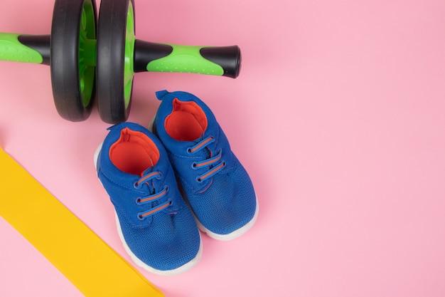 Sportieve gele elastische band. sportuitrusting. gele elastische band. groene halter. sportieve sneakers. training schoenen.