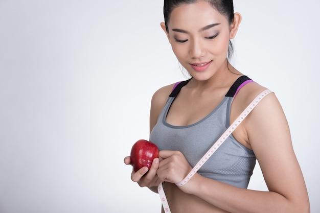 Sportieve geschiktheidsvrouw met het meten van band en rode appel die zich tegen witte muur bevinden