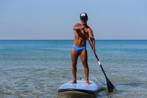 Sportieve gezonde persoon staat op zijn surfplank op het water en roeit door roeispaan. het concept van een sportieve en gezonde levensstijl.