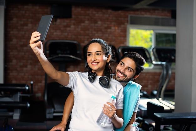 Sportieve indiase aziatische man en vrouw die rusten tussen oefeningen en smartphone gebruiken in de sportschool, iets presenteren of selfie-foto's maken