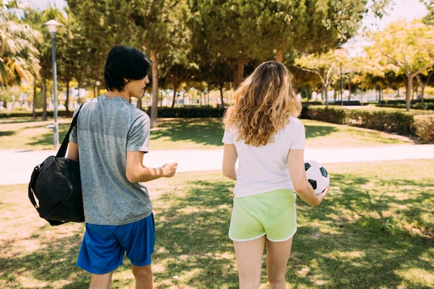 Sportieve jeugdvrienden die langs park lopen
