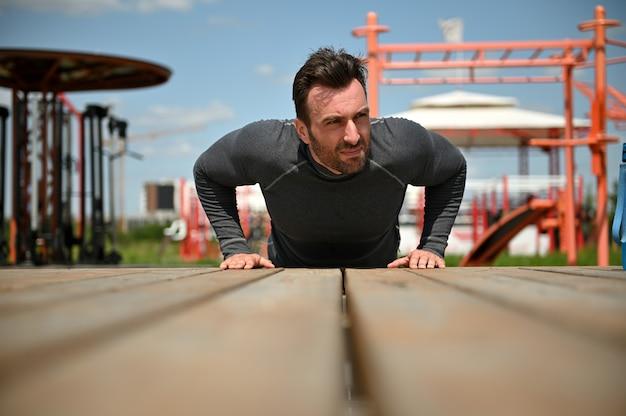 Sportieve jonge man doet push-ups op houten oppervlak buiten oefenen op sportveld achtergrond