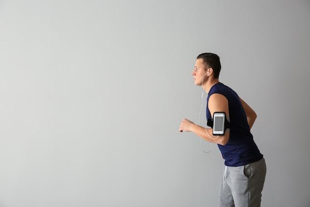 Sportieve jonge man loopt tegen een lichte achtergrond