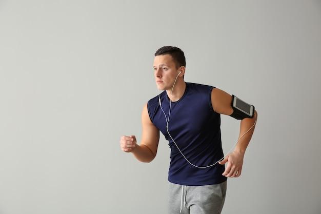 Sportieve jonge man loopt tegen lichte achtergrond