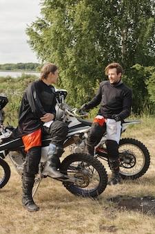 Sportieve jonge mannen in motoroutfits zittend op motoren en praten tijdens het rusten na race in het bos