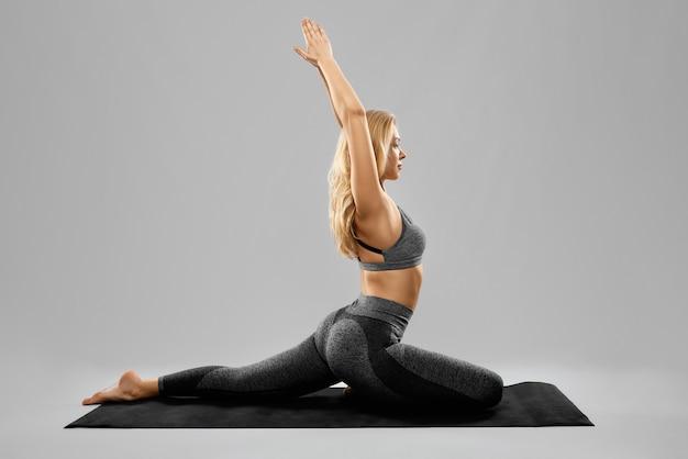 Sportieve jonge mooie vrouw die yogapraktijken op zwarte oefeningsmat doet die op grijs wordt geïsoleerd