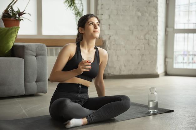 Sportieve jonge moslimvrouw die online yogalessen volgt en thuis oefent