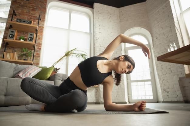 Sportieve jonge moslimvrouw die thuis yogalessen neemt