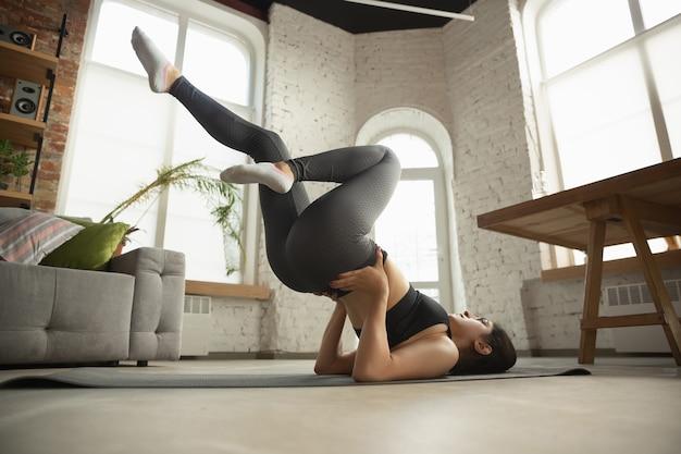Sportieve jonge moslimvrouw die thuis yogalessen neemt Gratis Foto