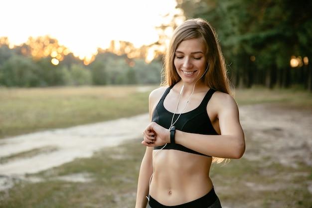 Sportieve jonge vrolijke vrouw die de horloges bekijkt, die de tijd na het lopen controleert