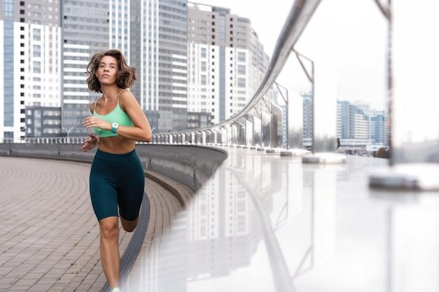 Sportieve jonge vrouw atleet draait op stedelijke straat in de ochtend