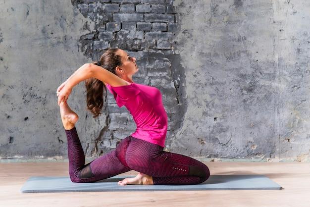 Sportieve jonge vrouw die één legged oefening van de koningsduif doet