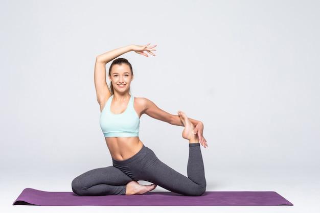Sportieve jonge vrouw die geïsoleerde yogapraktijk doet - concept van gezond leven en natuurlijk evenwicht tussen lichaam en geestelijke ontwikkeling