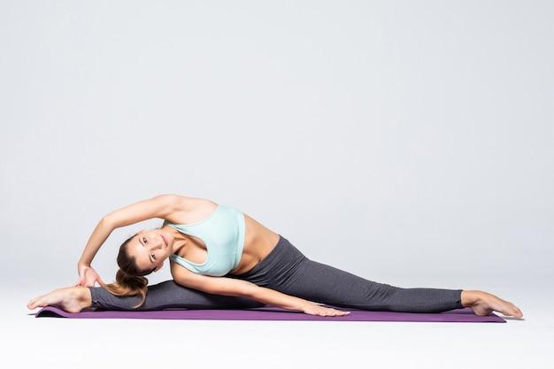 Sportieve jonge vrouw die geïsoleerde yogapraktijk doet. concept van gezond leven en natuurlijk evenwicht tussen lichaams- en mentale ontwikkeling. volledige lengte