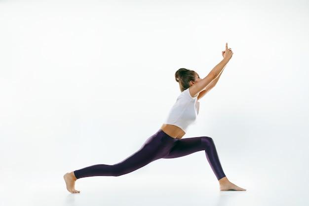 Sportieve jonge vrouw die geïsoleerde yogapraktijk doet. fit flexibel vrouwelijk model oefenen. concept van gezonde levensstijl en natuurlijk evenwicht tussen lichaam en geestelijke ontwikkeling.