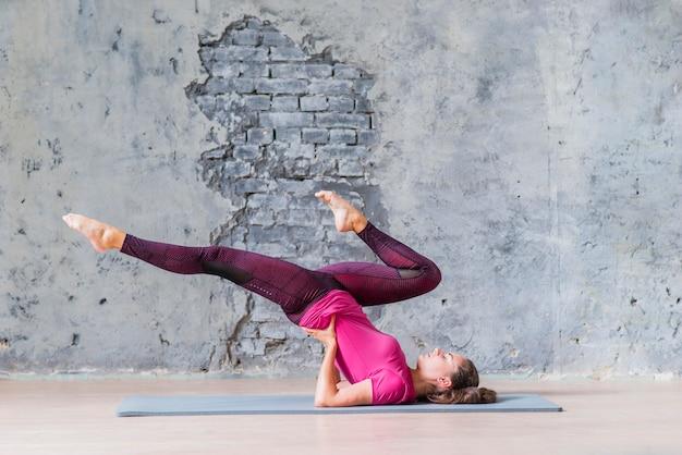 Sportieve jonge vrouw die geschiktheidsoefening doet tegen grijze achtergrond