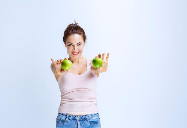 Sportieve jonge vrouw die groene appels aanbiedt