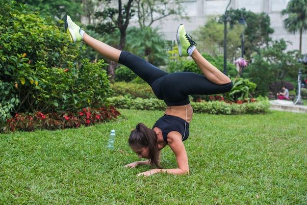 Sportieve jonge vrouw die handstandoefening met buigende benen op gras in park doet. fit meisje het beoefenen van yoga buitenshuis.