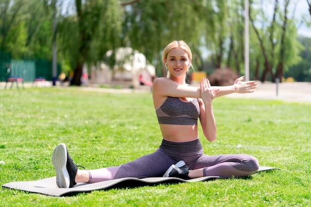 Sportieve jonge vrouw die het uitrekken doet zich