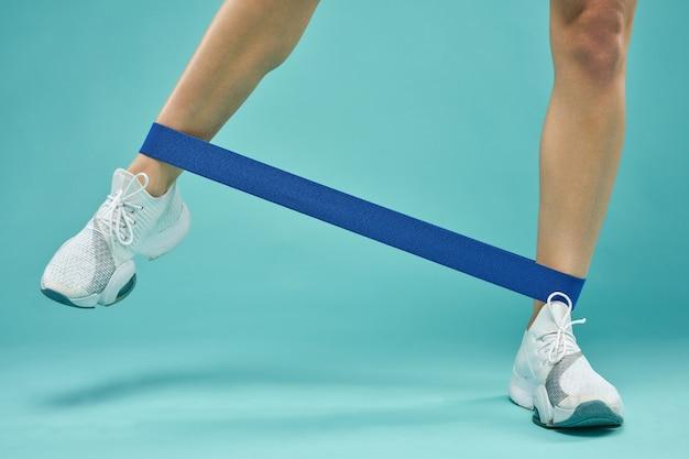 Sportieve jonge vrouw die oefening met fitnessband doet