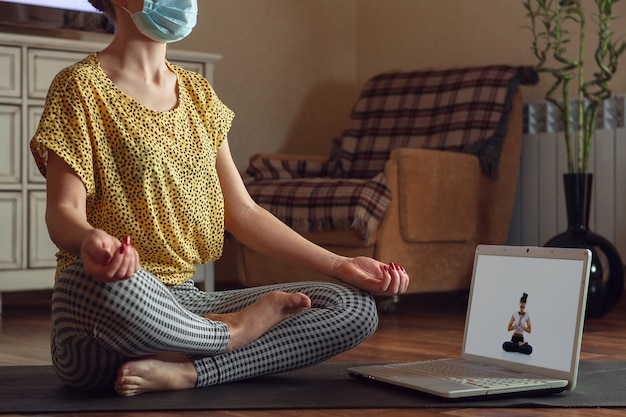 Sportieve jonge vrouw die online yogalessen volgt en thuis oefent terwijl ze in quarantaine is.