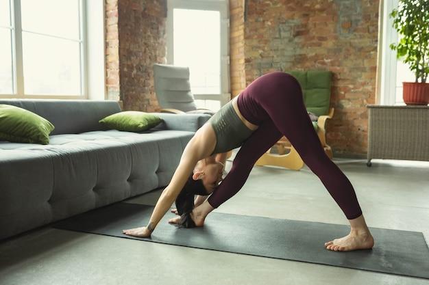 Sportieve jonge vrouw die thuis yoga beoefent