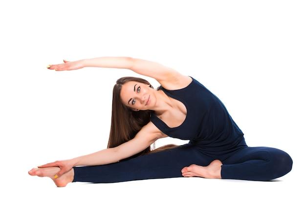 Sportieve jonge vrouw die yoga doet die op witte achtergrond wordt geïsoleerd