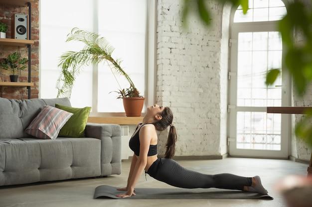Sportieve jonge vrouw die yogalessen online en praktijken thuis neemt