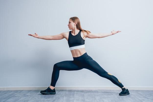 Sportieve jonge vrouw die yogapraktijk doet bij de gymnastiek.