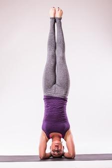 Sportieve jonge vrouw die yogapraktijk doet die op witte achtergrond wordt geïsoleerd - concept van gezond leven en natuurlijk evenwicht tussen lichaam en geestelijke ontwikkeling