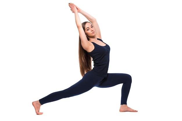 Sportieve jonge vrouw die yogapraktijk doet die op witte achtergrond wordt geïsoleerd