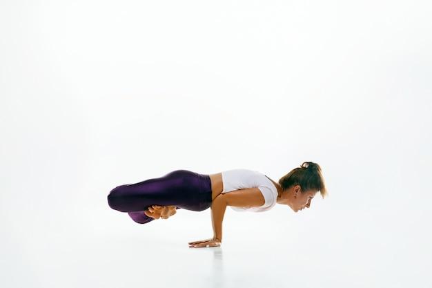 Sportieve jonge vrouw die yogapraktijk doet die op witte ruimte wordt geïsoleerd. fit flexibel vrouwelijk model oefenen