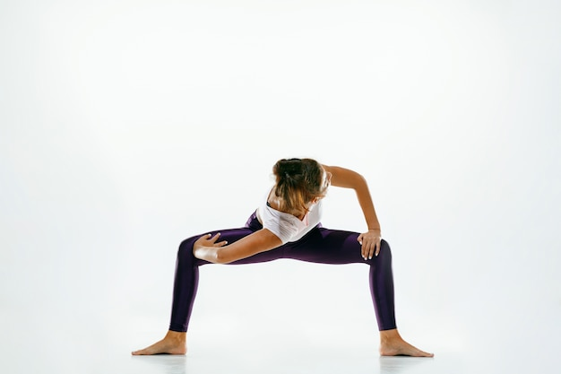 Sportieve jonge vrouw die yogapraktijk doet die op witte studioachtergrond wordt geïsoleerd. fit flexibel vrouwelijk model oefenen. concept van gezonde levensstijl en natuurlijk evenwicht tussen lichaam en geestelijke ontwikkeling.