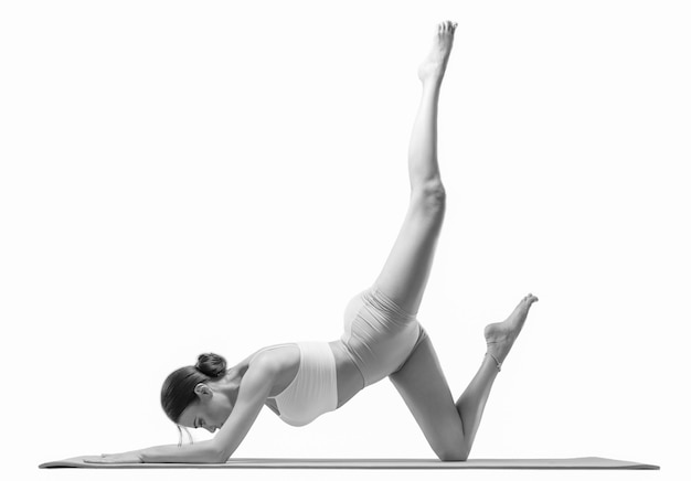 Sportieve jonge vrouw die yogapraktijken doet. geïsoleerd op een witte achtergrond. het concept van een gezonde levensstijl en natuurlijke balans tussen lichaam en mentale ontwikkeling. pilates, uitrekken.