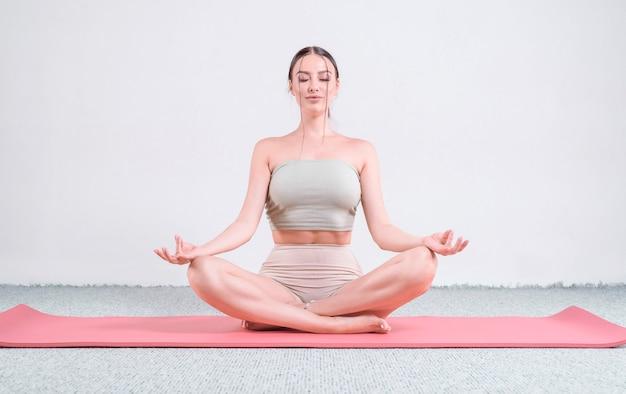 Sportieve jonge vrouw die yogapraktijken doet. het concept van een gezonde levensstijl en een natuurlijke balans tussen lichaam en geest. pilates, uitrekken. gemengde media