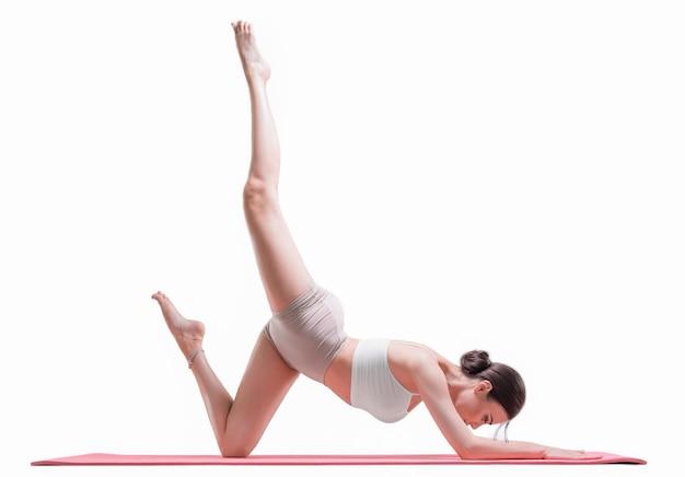 Sportieve jonge vrouw die yogapraktijken doet. stretchen en pilates poses. geïsoleerd op een witte achtergrond. gemengde media
