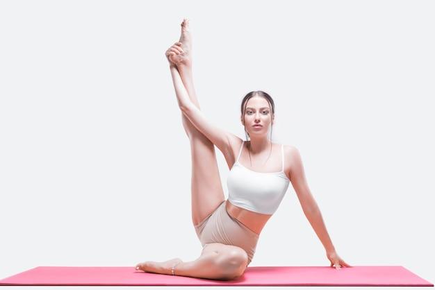 Sportieve jonge vrouw die yogapraktijken doet. ze zit op een rode mat met haar been omhoog. gemengde media