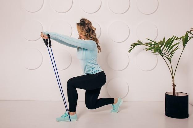 Sportieve jonge vrouw doet squat ochtendoefening alleen in de woonkamer, serieus fit meisje met sportkleding gehurkt trainingsspieren trainen thuis voor een gezond lichaam lifestyle concept, zijaanzicht