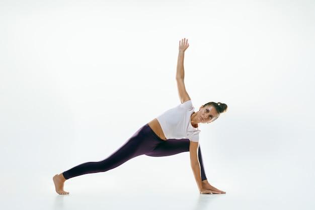 Sportieve jonge vrouw doet yoga praktijk geïsoleerd op wit