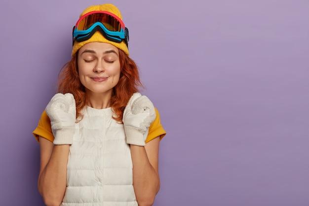 Sportieve jonge vrouw geniet van skiresort, balt vuisten met triomf, houdt de ogen dicht, draagt een beschermende snowboardbril, geïsoleerd over paarse studiomuur.