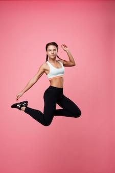 Sportieve jonge vrouw in blauwe top springen op zoek recht