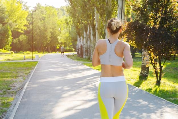 Sportieve jonge vrouw in sportkleding die in het park in de ochtend loopt