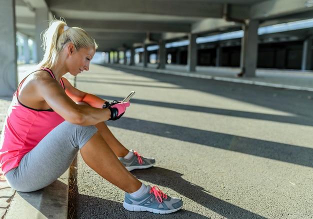 Sportieve jonge vrouw met behulp van een telefoon