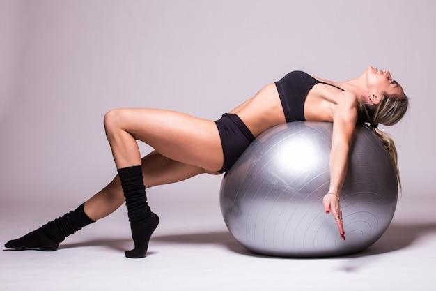 Sportieve jonge vrouw met een pilatesbal die over witte muur wordt geïsoleerd