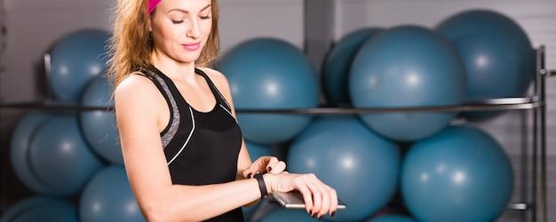 Sportieve jonge vrouw met fitnesstracker in de sportschool