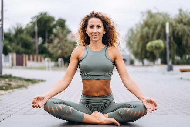 Sportieve jonge vrouw met lang haar in grijs trainingspak doen rekoefeningen op straat